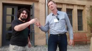 Dos personas mirando a cámara con copas en las manos, brindando.